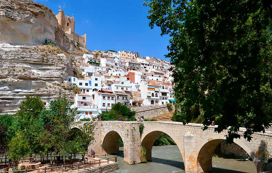 Puente romano de Alcalá del Júcar con el pueblo al fondo y el castillo en lo alto de la montaña.